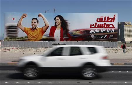 A car passes in front of an advertisement for the Bahrain Formula One Grand Prix in Manama, February 20, 2011. REUTERS/Hamad I Mohammed
