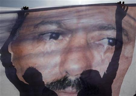 Anti-government protesters spread a poster of Yemen's President Ali Abdullah Saleh to deface it during a protest outside Sanaa University, February 21, 2011. REUTERS/Ammar Awad