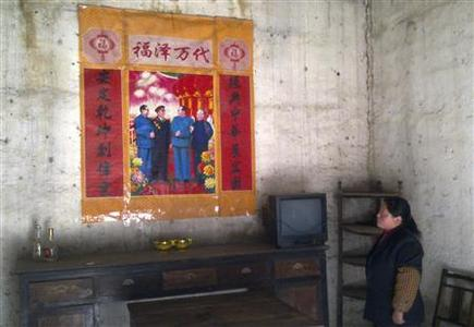 Villager Zhao Mengleng looks at a picture of the late Chinese leader Mao Zedong and other Communist revolutionary leaders, at her home in Zhaoyuan Village, where Premier Wen Jiabao visited during the Chinese New Year holidays to promote rural development, Anhui province, February 5, 2011. REUTERS/Chris Buckley