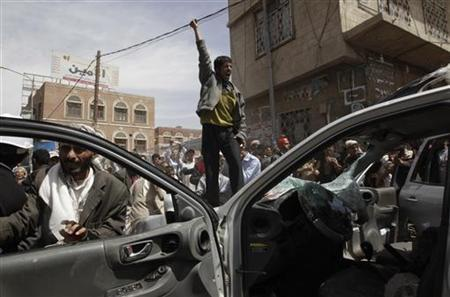 Anti-government protesters destroy a car belonging to government supporters outside Sanaa University, February 22, 2011. REUTERS/Ammar Awad
