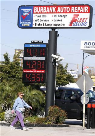 A woman walks past gasoline prices posted at Fleet Fueling in Burbank, February 22, 2011. REUTERS/Fred Prouser