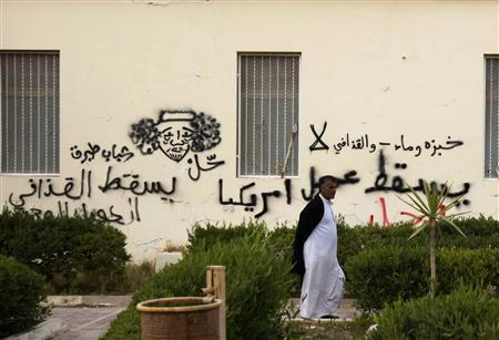A protester walks near anti-government graffiti near the main square of Tobruk February 22, 2011. REUTERS/Asmaa Waguih