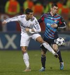 <p>Atacante do Olympique, Lyon Gomis, desafia Cristiano Ronaldo, do Real Madrid, durante a partida da Liga dos Campeões. 22/02/2011 REUTERS/Vincent Kessler</p>