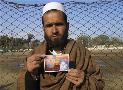 Yar Mohammad holds an image depicting pictures of his late father, Atta Mohammad, as he poses in Jalalabad February 19, 2011. Yar Mohammad was in Iran when his electrician father was taken from his home by U.S. and Afghan soldiers, beaten in a school bathroom and then shot in the head one afternoon last September. A U.S. soldier now faces trial for pulling the trigger, but Atta's family, part of the vast rural Afghan population whose support is vital to turning the tide in a decade-long war against Islamist insurgents, say they have been given no compensation and little sense of justice. Picture taken February 19, 2011. REUTERS/ Parwiz