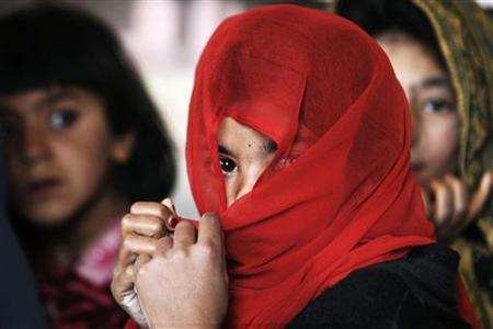 A girl covers her face with a scarf during class in the town of Kunjak in southern Afghanistan's Helmand province, February 21, 2011. REUTERS/Finbarr O'Reilly