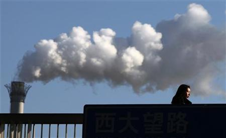 A woman walks across a bridge in front of a chimney billowing smoke from a coal-burning power station in central Beijing February 25, 2011. REUTERS/David Gray