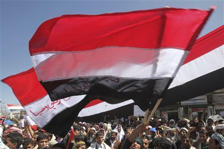 An anti-government protester waves Yemen's national flags during a protest demanding the ouster of Yemen's President Ali Abdullah Saleh outside Sanaa University February 28,2011. REUTERS/Khaled Abdullah