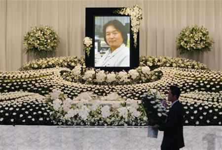 A funeral worker carries flowers in front of the casket of Reuters television cameraman Hiro Muramoto before a wake in Tokyo April 17, 2010. REUTERS/Michael Caronna