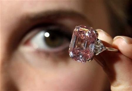 An employee poses with a 24.78 carat Fancy Intense Pink diamond at Sotheby's in London October 25, 2010. REUTERS/Luke MacGregor