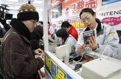 <p>Toyohisa Ishihara (esquerda), o primeiro da fila, compra o novo aparelho portátil de videogames Nintendo 3D em loja de eletrônicos em Tóquio, em 26 de fevereiro de 2011. REUTERS/Yuriko Nakao</p>