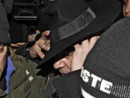 Fashion designer John Galliano is surrounded by policemen as he leaves a police station in Paris, February 28, 2011. REUTERS/Jacky Naegelen