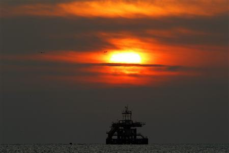 A sunset view of a floating oil platform along the Tirreno sea coast in front of the city of Civitavecchia, 70km (43 miles) north of Rome, February 26, 2011.REUTERS/Giampiero Sposito