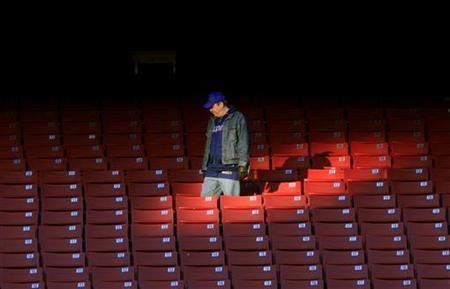 A New York Giants fan walks past empty seats at the Giants Stadium in East Rutherford, December 27, 2009. REUTERS/Mike Segar