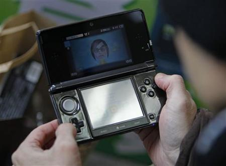 Toyohisa Ishihara, the first person to purchase Nintendo's 3DS game player, tries out a game in Tokyo February 26, 2011. REUTERS/Yuriko Nakao