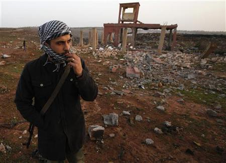 A rebel walks inside a destroyed weapons dump near Benghazi March 5, 2011. REUTERS/Suhaib Salem