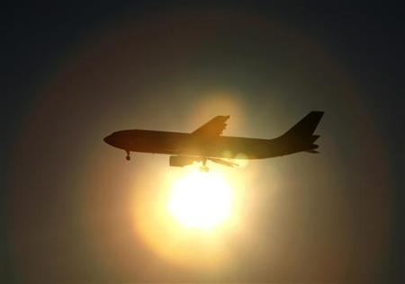 A Japan Airlines (JAL) aircraft is silhouetted against the setting sun as it prepares to land at Haneda airport in Tokyo January 17, 2010. REUTERS/Yuriko Nakao