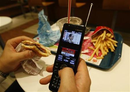 A man watches television through his mobile phone at a fast food restaurant in Tokyo July 10, 2009. REUTERS/Kim Kyung-Hoon
