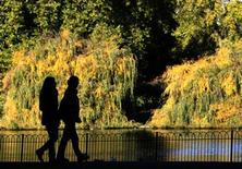 <p>A couple strolls on a sunny autumn day in St James's Park in London October 24, 2010. REUTERS/Luke MacGregor</p>