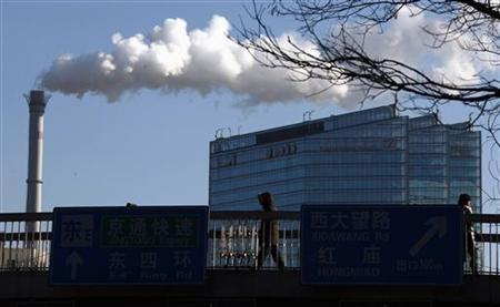 Pedestrians walk across a bridge in front of a chimney billowing smoke from a coal-burning power station in central Beijing February 25, 2011. REUTERS/David Gray