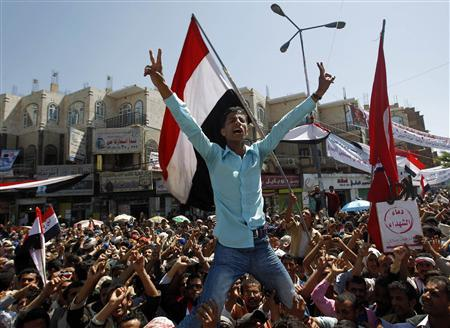 A protester is carried by fellow protesters as he shouts slogans during a rally outside Sanaa University March 9, 2011. REUTERS/Khaled Abdullah