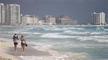 A couple walks along Marlin beach in Cancun February 1, 2011. REUTERS/Gerardo Garcia