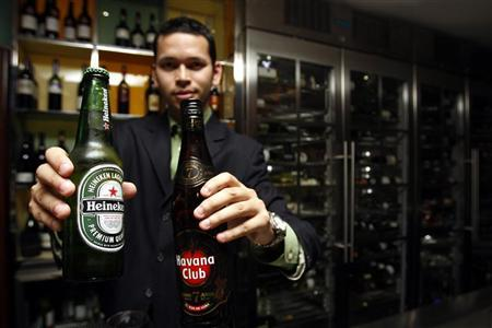 A waiter holds up bottles of alcoholic drinks at a bar in Dubai March 9, 2011. REUTERS/Abdullah Muhsen