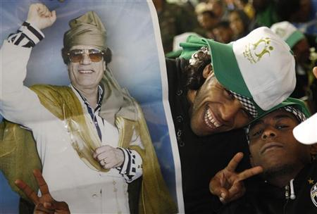 Supporters pose with a picture of Libya's leader Muammar Gaddafi during a youth rally in Tripoli March 10, 2011. REUTERS/Chris Helgren