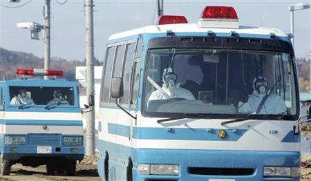 Police wearing protective clothing and respirators head towards the Fukushima Daiichi Nuclear Plant in trucks in Minamisouma City, Fukushima Prefecture March 12, 2011. REUTERS/Yomiuri
