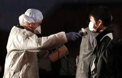 <p>Official in protective gear scans for signs of radiation on a man who is from the evacuation area near the Fukushima Daini nuclear plant in Koriyama, March 13, 2011. REUTERS/Kim Kyung-Hoon</p>