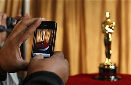 A man photographs an Oscar statuette using his phone at the ''Meet the Oscars'' exhibit at Grand Central Station in New York February 23, 2011. REUTERS/Brendan McDermid