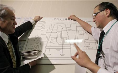Tokyo Electric Power officials hold an illustration of a nuclear plant as they answer reporters' questions at the disaster center in Fukushima, northern Japan March 15, 2011. REUTERS/Yuriko Nakao