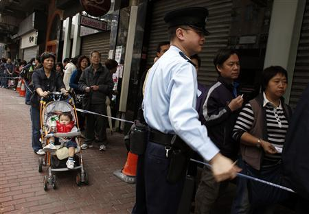 A policeman maintains order as people wait in line outside a store to buy Japanese milk powder in Hong Kong March 15, 2011.REUTERS/Bobby Yip