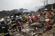 <p>Спасатели ищут выживших людей в японском городе Оцути, 15 марта 2011 года. Мощнейшее за всю историю наблюдений землетрясение на северо-востоке Японии, возникшее в пятницу и вызвавшее после себя разрушительное цунами, могло унести жизни более 10.000 человек. REUTERS/Damir Sagolj</p>