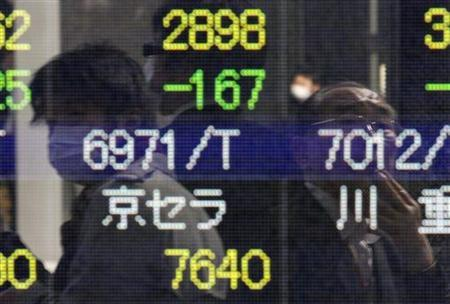 People are reflected in a screen displaying stock prices in Tokyo March 14, 2011. REUTERS/Issei Kato