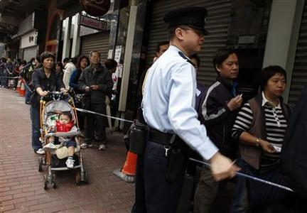 A policeman maintains order as people wait in line outside a store to buy Japanese milk powder in Hong Kong March 15, 2011. Hundreds of people in the territory, worried that future Japanese made milk powder would be contaminated by radiation, lined up for the product. REUTERS/Bobby Yip