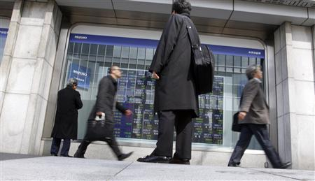 People look at a screen displaying stock prices in Tokyo March 14, 2011. REUTERS/Issei Kato