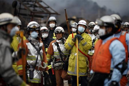 Civil defence relief workers stand together after an earthquake and tsunami swept through Otsuchi, in the Iwate prefecture, eastern Japan March 15, 2011. REUTERS/International Red Cross/Handout