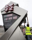 <p>Techniciens à l'oeuvre pour remettre en état de marche l'horloge marquant le compte à rebours avant les Jeux olympiques de 2012, à Londres. L'horloge digitale s'est figée lundi, quelques heures à peine après sa mise en route. /Photo prise le 15 mars 2011/REUTERS/Andrew Winning</p>