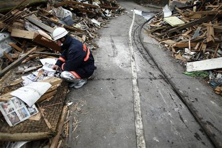 A firemen goes through pictures found in ruins of the devastated residential area of tsunami hit Otsuchi March 15, 2011. REUTERS/Damir Sagolj