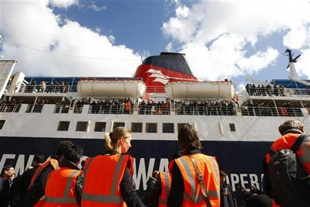 Embassy officials wait to board the German-chartered ferry Santorini Express after it berthed with some 500 oil workers of various nationalities from the Benghazi area of Libya on board in Valletta's Grand Harbour March 1, 2011. REUTERS/Darrin Zammit Lupi