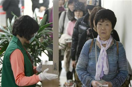 Travellers from Japan line up to go through a screening gate as staff from Taiwan's Atomic Energy Council monitors the radiation level on them at Taipei's Songshan airport March 17, 2011. REUTERS/Pichi Chuang