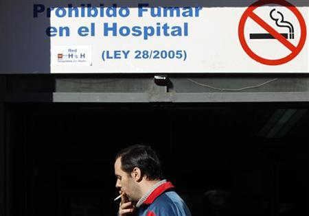 A man smokes a cigarette near an entrance to a hospital in Madrid January 1, 2011. REUTERS/Susana Vera