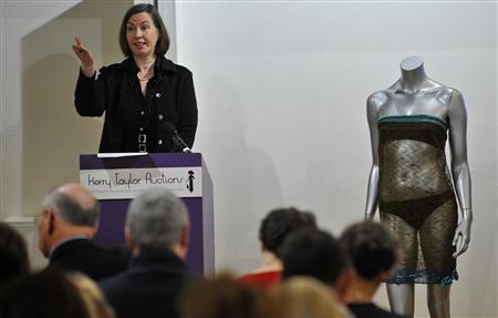 The see-through knitted dress (R), as modelled by the fiancee of Britain's Prince William, Kate Middleton at the annual St Andrew's University charity fashion show in 2002, (R) is displayed as auctioneer Kerry Taylor takes bids for other items, during an auction in central London March 17, 2011. REUTERS/Toby Melville