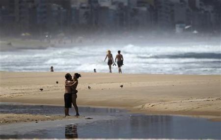 A couple embrace at Leblon Beach in Rio de Janeiro March 16, 2011. REUTERS/Ricardo Moraes