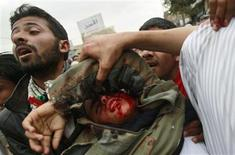 <p>Anti-government protesters carry an injured fellow protester in Sanaa March 18, 2011. REUTERS/Khaled Abdullah</p>