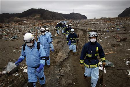 Rescue workers make their way through an area devastated by a tsunami as they search for victims in Rikuzentakat March 21, 2011. REUTERS/Damir Sagolj