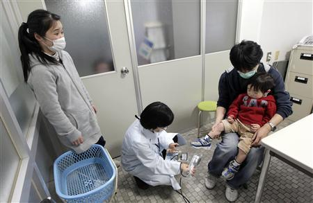 Kosuke Sato, sitting on the lap of his father Kazumi, from Soma in Fukushima, undergoes a screening test for signs of nuclear radiation by a doctor as his mother Maki looks on at a welfare center in Yonezawa, northern Japan, 98 km (61 miles) from the Fukushima nuclear plant, March 21, 2011. REUTERS/Yuriko Nakao