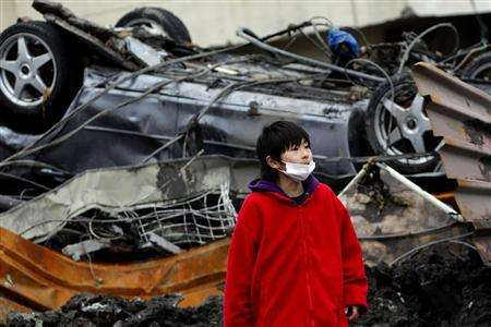 A boy looks on in front of an overturned car among debris in Otsuchi, Iwate prefecture March 21, 2011, after an earthquake and tsunami hit the area on March 11. REUTERS/Aly Song