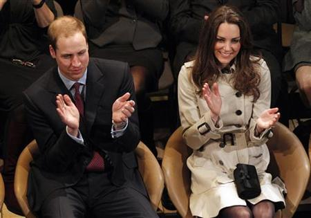Britain's Prince William and his fiancee, Kate Middleton, applaud as they watch a play at the Youth Action Northern Ireland Centre, in Belfast, Northern Ireland March 8, 2011. REUTERS/Phil Noble