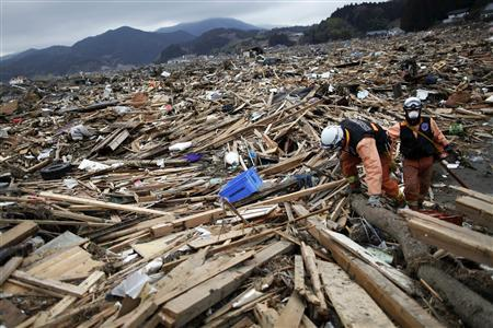 Rescue workers make their way through a sea of debris as they search for victims of a tsunami in devastated Rikuzentakat March 21, 2011. REUTERS/Damir Sagolj